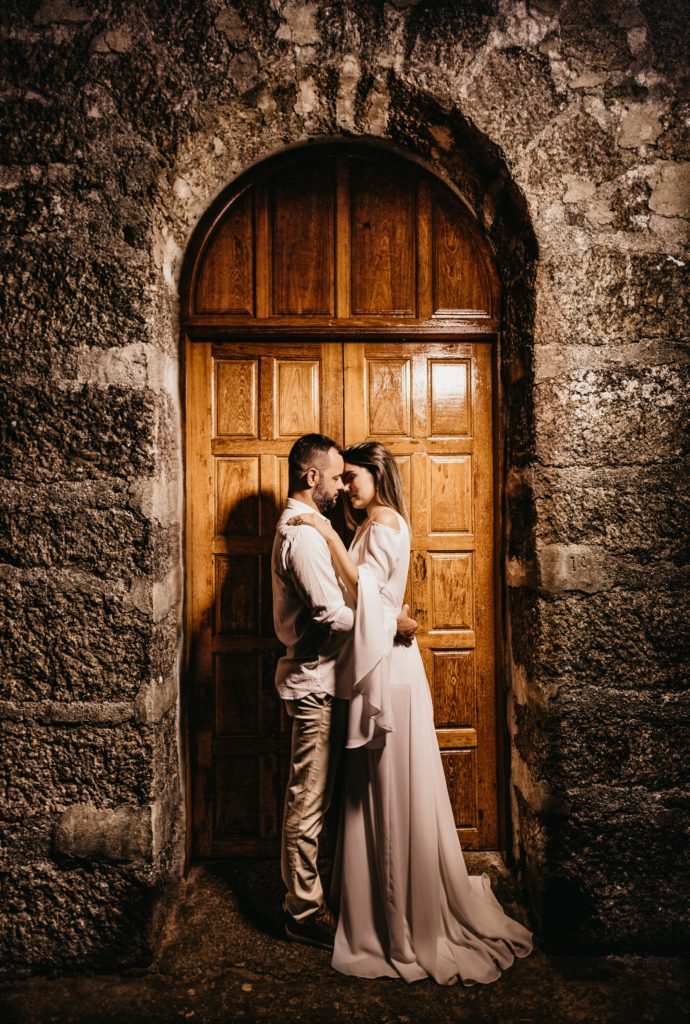 Couple on their wedding day standing in front of the church doors.